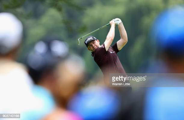 Spectators watch as Branden Grace of South Africa plays his second shot on the 4th hole during Day One of The BMW South African Open Championship at...