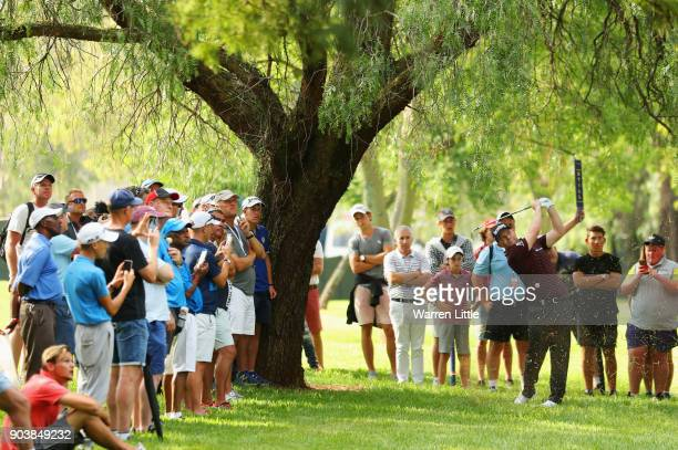 Spectators watch as Branden Grace of South Africa plays his second shot on the 18th hole during Day One of The BMW South African Open Championship at...