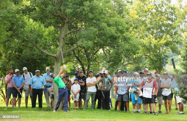 Spectators watch as Charl Schwartzel of South Africa plays his second shot on the 18th hole during Day One of The BMW South African Open Championship...