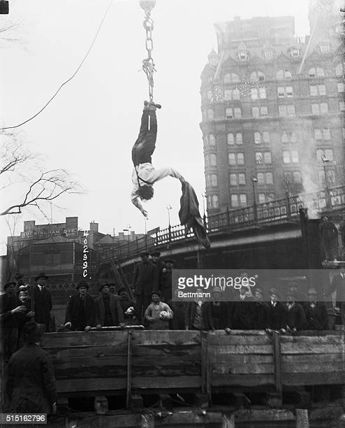 Spectators watch as escape artist Harry Houdini frees himself from a straightjacket while he hangs from a hook above a subway