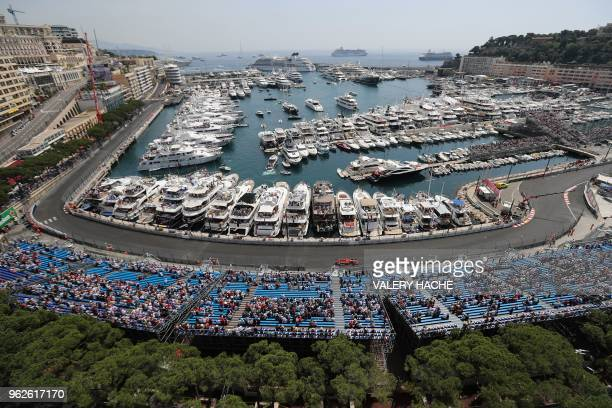 Spectators watch as Ferrari's German driver Sebastian Vettel drives during the third practice session at the Monaco street circuit on May 26, 2018 in...