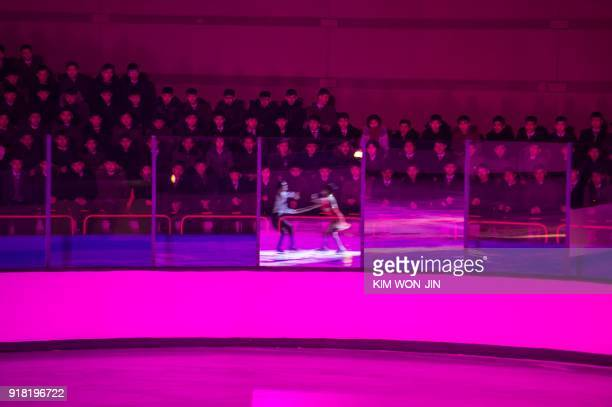 Spectators watch as figure skaters perform during the opening ceremony of a figure skating festival marking the anniversary of the birth of late...