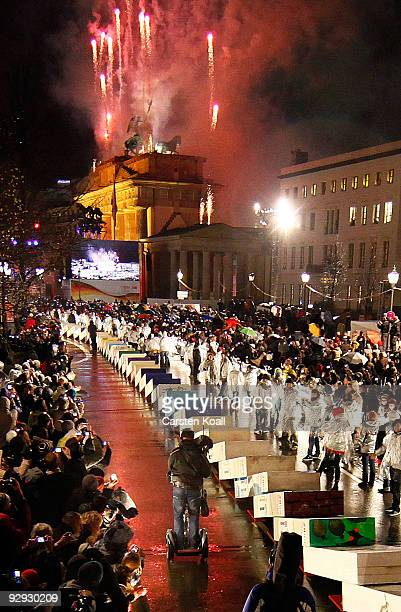 Spectators watch as giant painted styrofoam dominoes topple along the route of the former Berlin Wall near the Brandenburg Gate on November 9 2009 in...