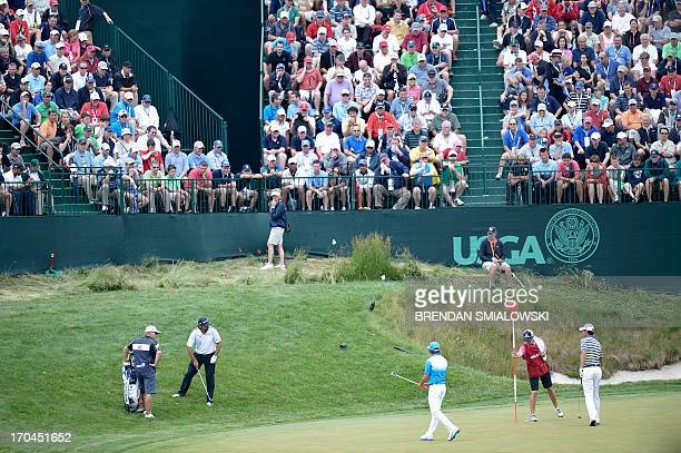 Spectators watch as golfers Jason Day of Australia Rickie Fowler of the United States and Matteo Manassero of Italy play on the 17th green during the...