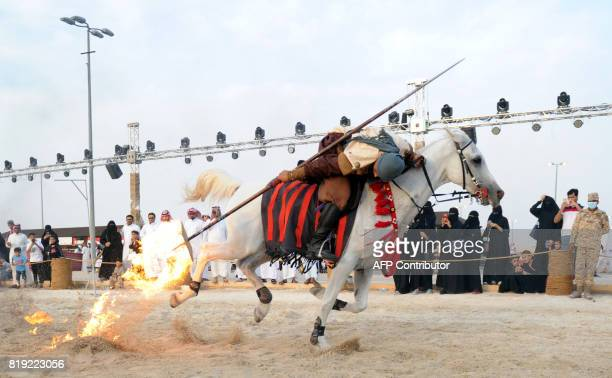 Spectators watch as horseman performs with a lance at the Souk Okaz Festival in the Saudi city of Taif on July 19 2017 The 10day cultural festival a...