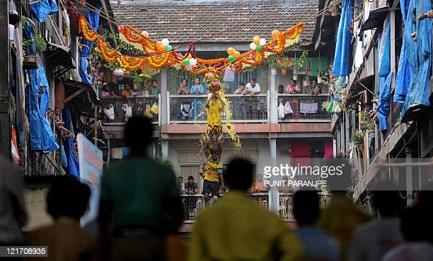 Spectators watch as Indian Hindu devotees form a human pyramid to break the 'dahihandi' in Mumbai on August 22 as part of celebrations of...