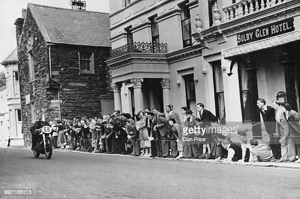 Spectators watch as Johnny Lockett of Great Britain riding the Norton 348cc motorcycle passes the Sulby Glen Hotel during the Isle of Man Junior TT...