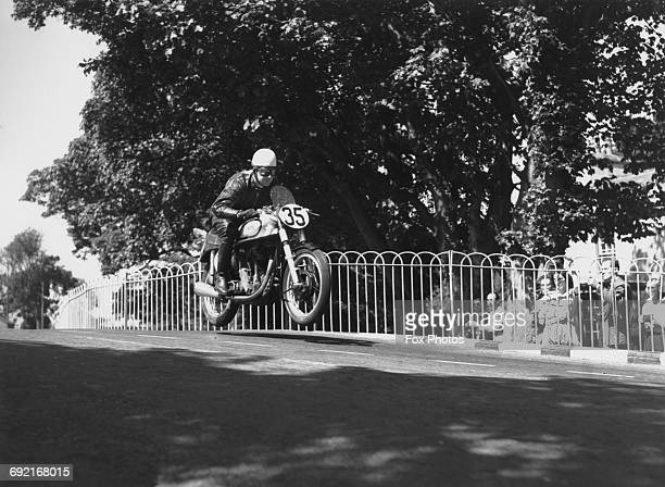 Spectators watch as Johnny Lockett of Great Britain riding the Norton 350cc motorcycle becomes airborne over Bellaugh Bridge during the Isle of Man...