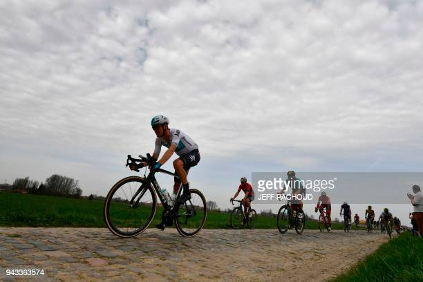 Spectators watch as Netherland's Dylan Van Baarle competes during the 116th edition of the ParisRoubaix oneday classic cycling race between Compiegne...