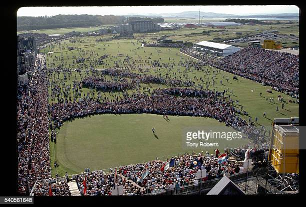 Spectators watch as professional golfers play the 18th hole during the British Open at the Royal and Ancient Golf Club