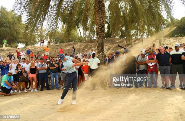 Spectators watch as Rory McIlroy of Northern Ireland plays his second shot on the 8th hole during the final round on day four of the Omega Dubai...