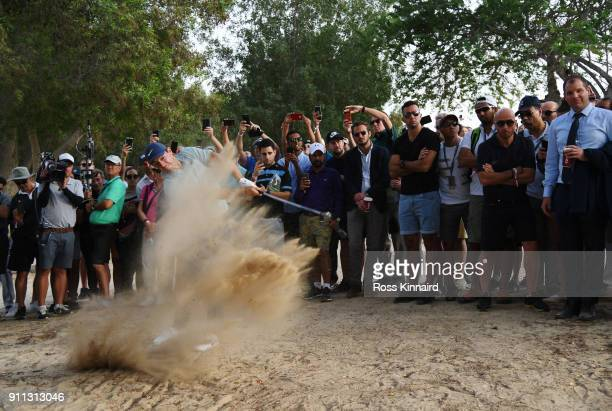 Spectators watch as Rory McIlroy of Northern Ireland plays his second shot on the 16th hole during the final round on day four of the Omega Dubai...