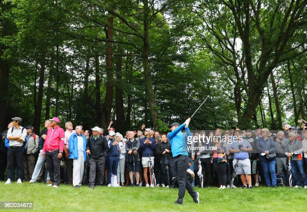 Spectators watch as Rory McIlroy of Northern Ireland plays his second shot on the 3rd hole during day one of the BMW PGA Championship at Wentworth on...