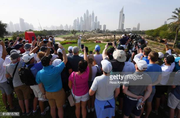 Spectators watch as Rory McIlroy of Northern Ireland tees off on the 8th hole during day three of Omega Dubai Desert Classic at Emirates Golf Club on...