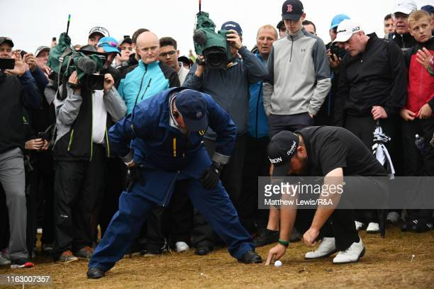Spectators watch as Shane Lowry of Ireland and an official discuss a drop on the 17th hole during the second round of the 148th Open Championship...