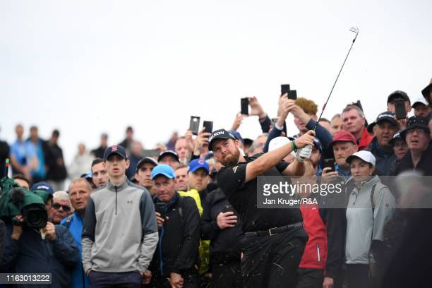 Spectators watch as Shane Lowry of Ireland hits his second shot during the second round of the 148th Open Championship held on the Dunluce Links at...