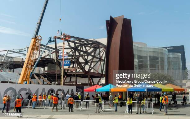 Spectators watch as the last structural beam is put into place at the Orange County Museum of Art in Costa Mesa, CA on Tuesday, October 6, 2020. The...