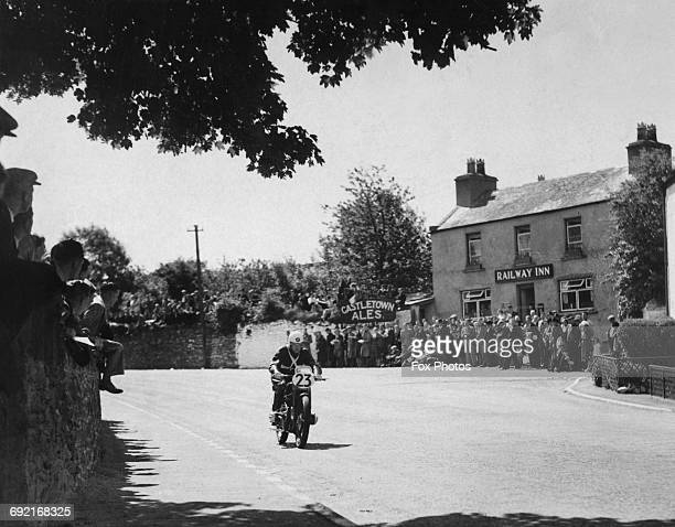 Spectators watch as Tim Reid of Great Britain riding the BMW Motorrad 500cc motorcycle passes the Railway Arms public house pub near Union Mills...