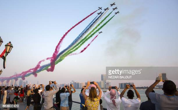 TOPSHOT Spectators watch as UAE's AlFursan National Aerobatic Team performs with smoke along the corniche of the capital Abu Dhabi on December 1...