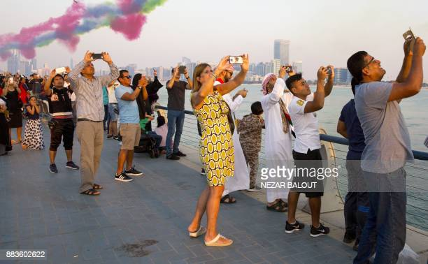 Spectators watch as UAE's AlFursan National Aerobatic Team performs with smoke along the corniche of the capital Abu Dhabi on December 1 during...