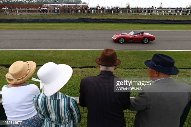 Spectators watch cars taking part in a practice session for the Sussex Trophy, a race for sports cars from 1955 to 1960 at the Goodwood Revival 2021,...