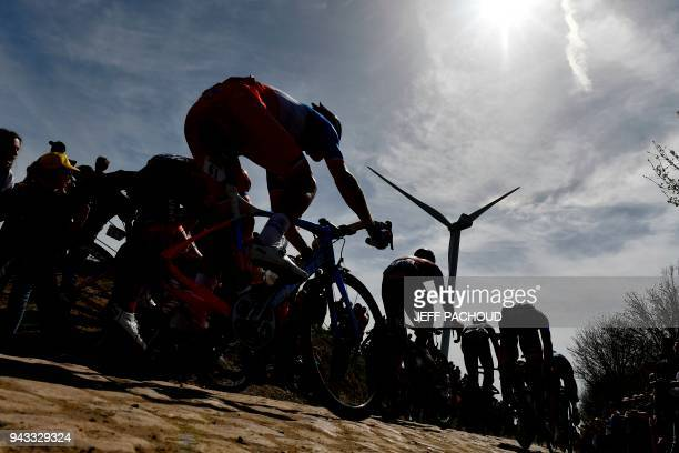 Spectators watch cyclists as they drive across cobbled stone during the 116th edition of the ParisRoubaix oneday classic cycling race between...