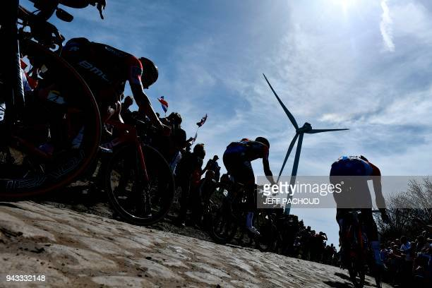 TOPSHOT Spectators watch cyclists as they drive across cobbled stone during the 116th edition of the ParisRoubaix oneday classic cycling race between...