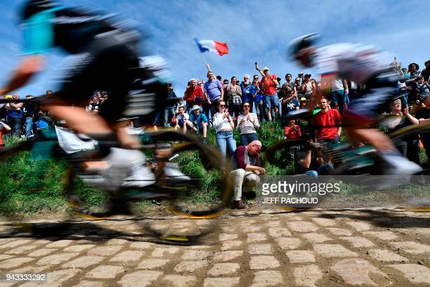 Spectators watch cyclists as they drive across cobbled stone during the 116th edition of the Paris-Roubaix one-day classic cycling race, between...