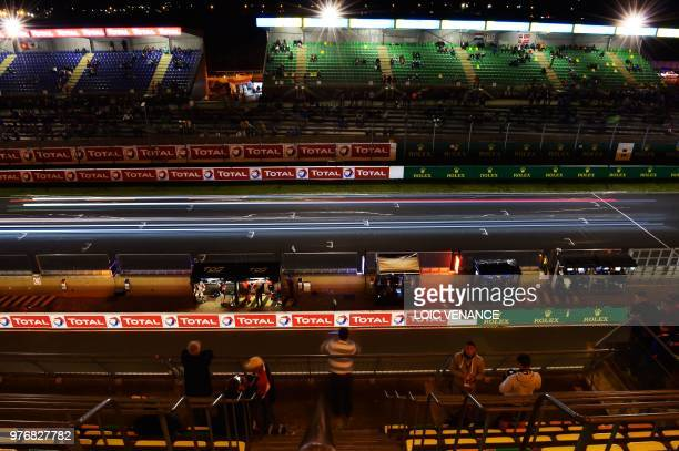 Spectators watch drivers compete during the 86th Le Mans 24hours endurance race at the Circuit de la Sarthe at night on June 17 2018 in Le Mans...