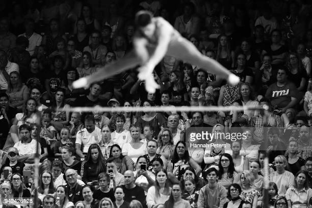 Spectators watch Frank Baines of Scotland as he competes on the horizontal bar in the Men's Team Final and Individual Qualification on day one of the...