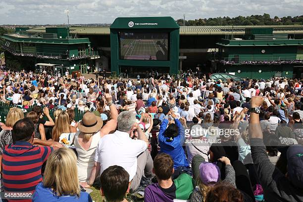Spectators watch from a big screen Britain's Andy Murray play Canada's Milos Raonic in the men's singles final match on the last day of the 2016...