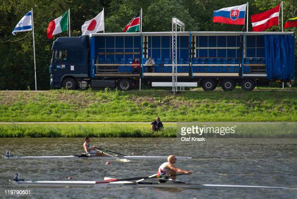 Spectators watch from a moving truck alongside the track during Day Four of the FISA World Rowing Under 23 Championships 2011 on the Bosbaan on July...