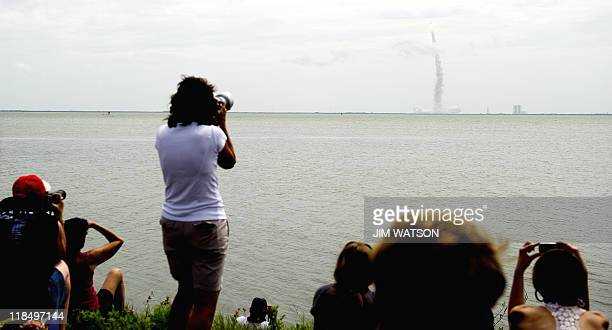 Spectators watch from a park in Titusville, Florida, as the space shuttle Atlantis launches from Kennedy Space Center on July 8, 2011 for the final...