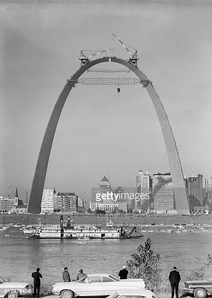 Spectators watch from across the Mississippi River as cranes carefully maneuver the final section of the Gateway Arch into place Symbolizing the...