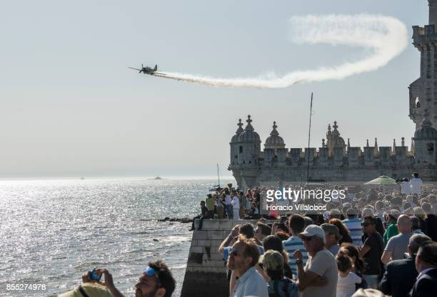 Spectators watch from Belem Tower a Yakovlev Yak52 performing aerobatics over Tagus River during the commemoration of the 100th anniversary of...