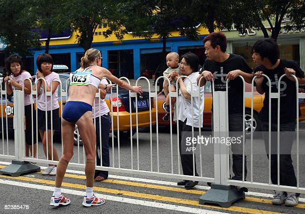 Spectators watch Marathon world record holder Britain's Paula Radcliffe stretching while suffering during the 2008 Beijing Olympic Games women's...