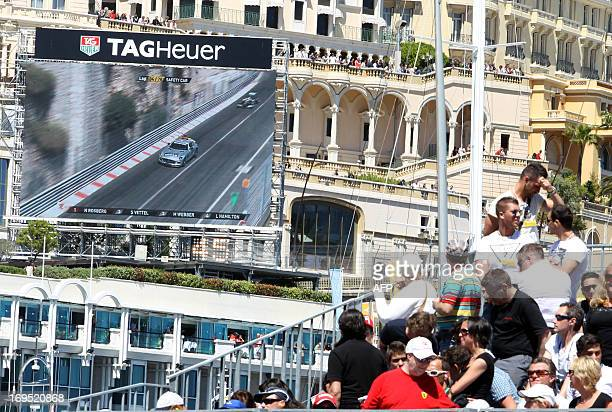 Spectators watch Mercedes' German driver Nico Rosberg follow the safety car on a giant screen during the Monaco Formula One Grand Prix at the Circuit...