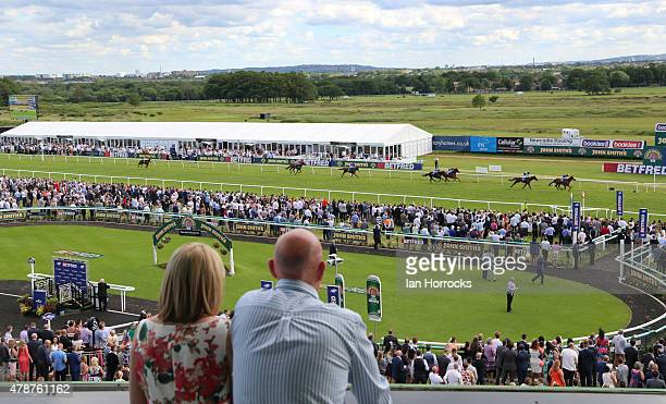 Spectators watch on as Gerry The Glover ridden by Silvestra De Sousa wins the The Betfred Keep it Funny Handicap Stakes during The Northumberland...