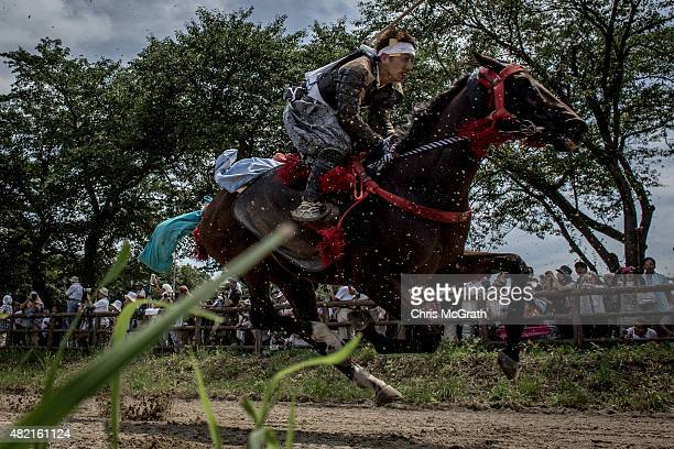 Spectators watch on as Samurai horseman competes in the Kacchukeiba during the Soma Nomaoi festival at Hibarigahara field on July 26 2015 in...