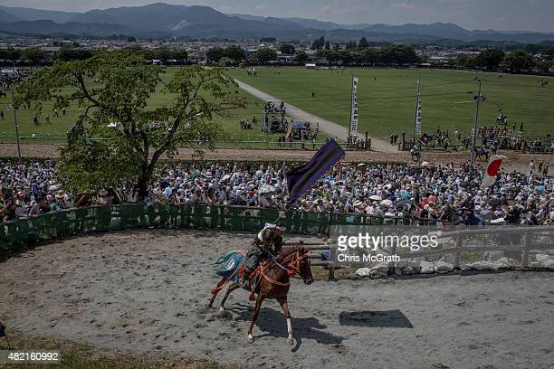 Spectators watch on as Samurai horseman rides up to the winners circle after competing in the Kacchukeiba during the Soma Nomaoi festival at...