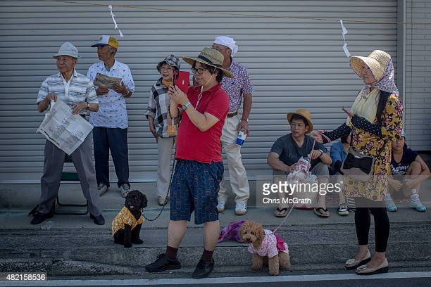 Spectators watch on as Samurai horsemen parade down a street during the Soma Nomaoi festival on July 26 2015 in Minamisoma Japan Every summer the...