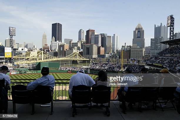Spectators watch opening day action between the Los Angeles Dodgers and the Pittsburgh Pirates with the Pittsburgh skyline as a backdrop on April 10...