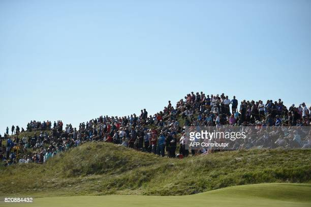 Spectators watch play on the 8th green during on day three of the Open Golf Championship at Royal Birkdale golf course near Southport in north west...