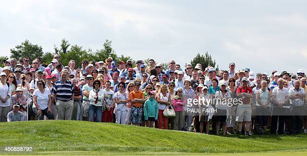 Spectators watch players on the18th hole during the opening day of the Irish Open at the Fota Island Resort in Cork Ireland on June 19 2014...