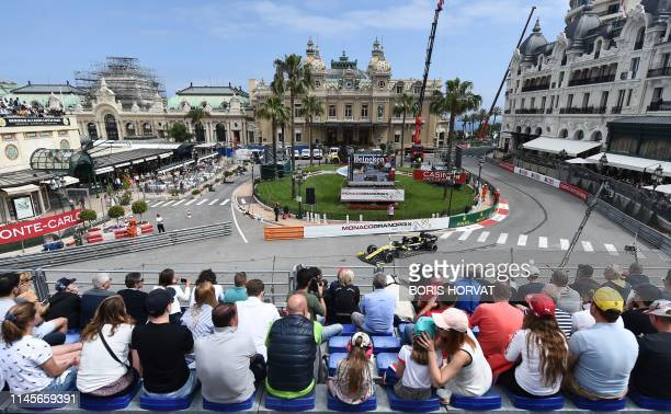 Spectators watch Renault's Australian driver Daniel Ricciardo driving during the second practice session at the Monaco street circuit on May 23, 2019...