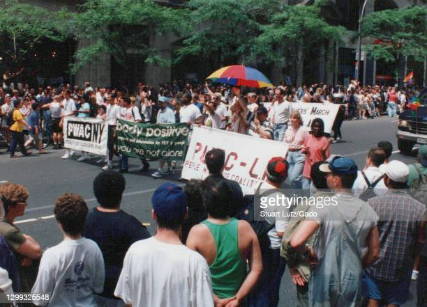 """Spectators watch representatives carry """"People With AIDS Coalition"""" and """"body positive"""" banners on Fifth Avenue, participating in the annual NYC..."""