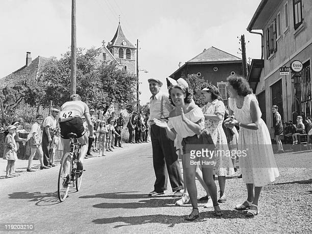 Spectators watch riders passing through a village during the Tour de France July 1951 Original publication Picture Post 5381 The Greatest Show On...