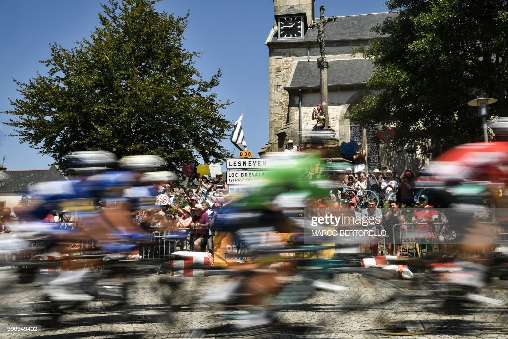 Spectators watch riders speeding through the village of Plouvien, during the sixth stage of the 105th edition of the Tour de France cycling race between Brest and Mur-de-Bretagne Guerledan, western France, on July 12, 2018.