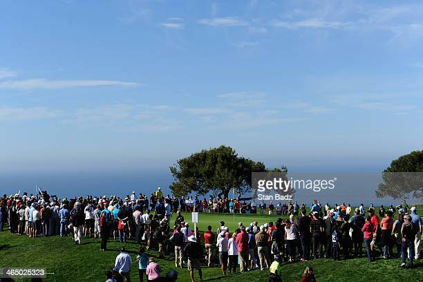 Spectators watch Stewart Cink putt on the 6th green during the third round of the Farmers Insurance Open on Torrey Pines South on January 25, 2014 in...