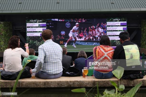 Spectators watch the action on a giant screen on the first day of the 2021 Wimbledon Championships at the The All England Tennis Club in Wimbledon,...
